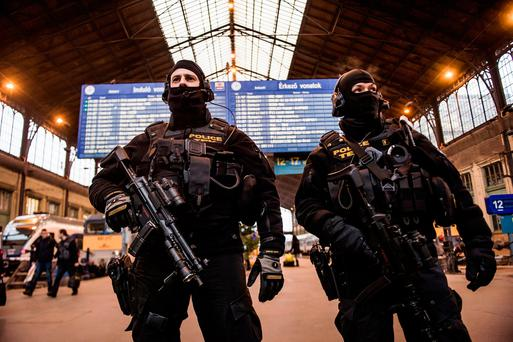 Police officers of the Counter Terrorism Centre with sub-machine guns stand guard at Nyugati Railway Station in central Budapest, Hungary Photo: AP