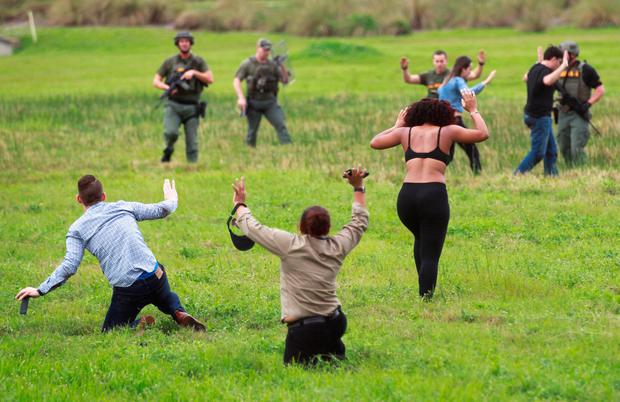 Law enforcement officers move in to verify the identity of people in this field just outside the airport perimeter following a shooting incident at Fort Lauderdale-Hollywood International Airport in Fort Lauderdale (Photo: Reuters)