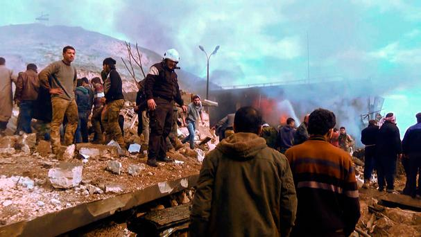 An image grab taken from an AFPTV video released on January 7, 2017 shows people gathering amidst the debris at the site of a car bomb attack in the rebel-held town of Azaz in northern Syria (Photo: Getty)