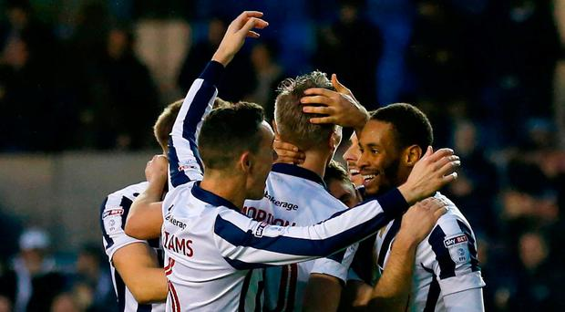Millwall's English-born Jamaican defender Shaun Cummings (R) celebrates with teammates after scoring their second goal during the English FA Cup third round football match between Millwall and Bournemouth at The Den