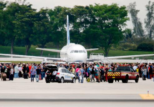 Runaway chaos: People stand on the tarmac at Fort Lauderdale-Hollywood International Airport last Friday after a gunman opened fire inside the terminal Photo: AP Photo/Lynne Sladky