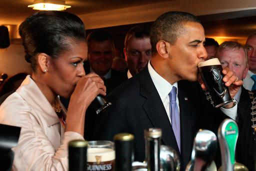 Thirsty work: Michelle and Barack Obama enjoy a drink of Guinness at Ollie Hayes Bar in Moneygall, Co Offaly - the president's ancestral home - on their previous trip to Ireland in 2011 Photo: MAXWELLS DUBLIN
