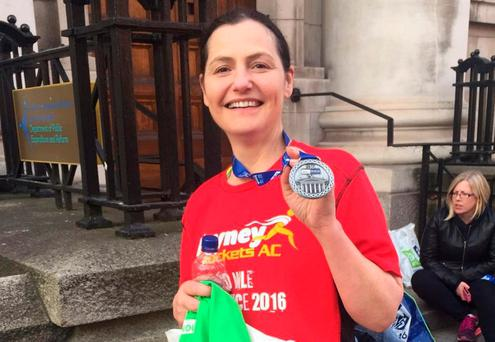 Road accident victim Mona Clarke proudly displays her medal after she completed the Dublin Marathon last October