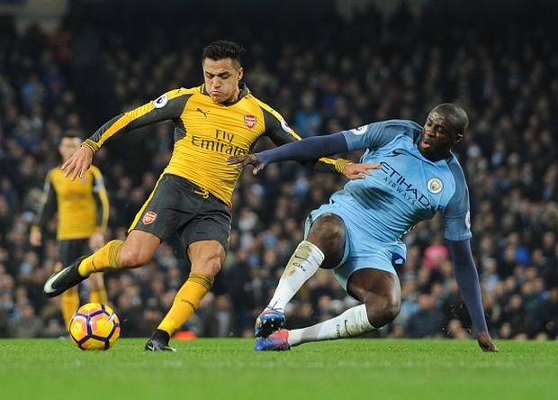 MANCHESTER, ENGLAND - DECEMBER 18: Alexis Sanchez of Arsenal challenged by Yaya Toure of Man City during the Premier League match between Manchester City and Arsenal at Etihad Stadium on December 18, 2016 in Manchester, England. (Photo by Stuart MacFarlane/Arsenal FC via Getty Images)