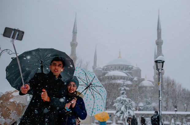 A couple takes a selfie in the Sultanahmet district, one of Istanbul's main tourist attractions, Monday, Jan. 9, 2017. (AP Photos/Emrah Gurel)