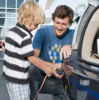 Aather and son charging their electric car