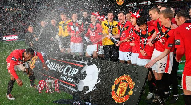 The Manchester United squad celebrates with the Carling Cup trophy in 2010