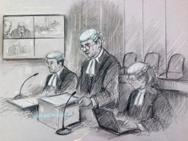 Court artist sketch by Elizabeth Cook of (left to right) defence lawyer Stephen Vullo, prosecutor Jonathan Rees and his supporting barrister (no name given) sitting in front of three empty chairs where Rolf Harris would have sat with dock officers - instead he can be seen appearing via video link (top left) - at Southwark Crown Court, London. Harris is accused of seven counts of indecent assault and one of sexual assault.Photo: Elizabeth Cook/PA Wire