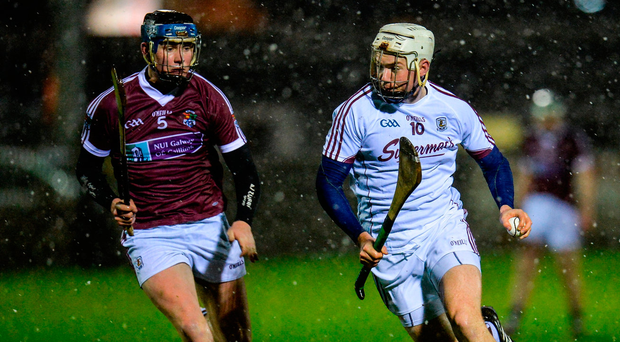 Galway's Padraig Brehony (right) tries to get away from Mike Connelly of NUI Galway as the teams battle through the snow showers during last night's Bórd na Mona Walsh Cup Group 1 clash at Ballinasloe Photo Seb Daly/Sportsfile