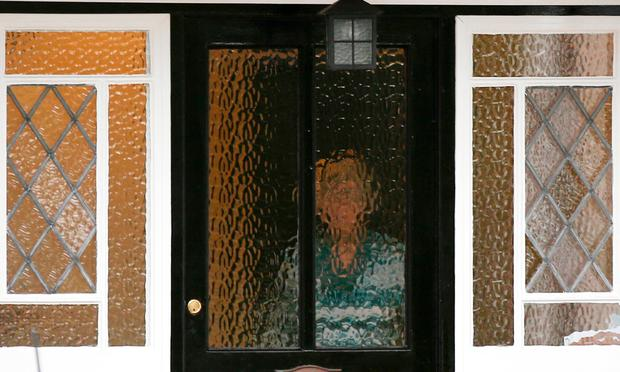 A person stands behind textured glass at an address which has been linked by local media to former British intelligence officer Christopher Steele, who has been named as the author of an intelligence dossier on President-elect Donald Trump, in Wokingham, Britain, January 12, 2016. REUTERS/Peter Nicholls
