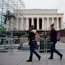 Tourists walk past scaffolding being put up as part of a stage to be used in the presidential inauguration in Washington next Friday. Photo: Getty Images
