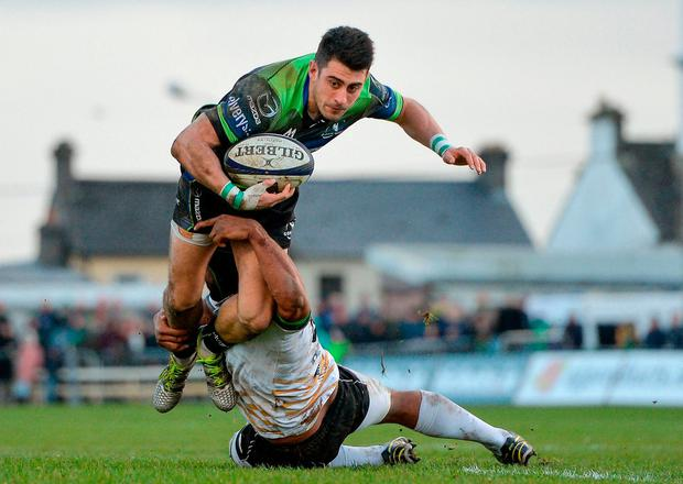 Connacht's Tiernan O'Halloran is tackled by Zebre's Maxime Mbandà. Photo: Seb Daly/Sportsfile