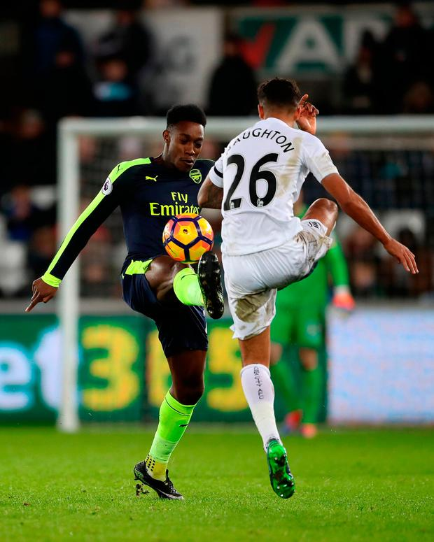 Arsenal's Danny Welbeck (left) and Swansea City's Kyle Naughton battle for the ball. Photo: PA