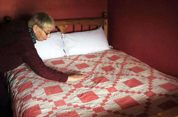 Margaret Gallagher making the bed in her thatched cottage in Belcoo