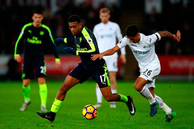 Arsenal's Alex Iwobi (left) and Swansea City's Kyle Naughton battle for the ball. Photo credit: Nick Potts/PA Wire