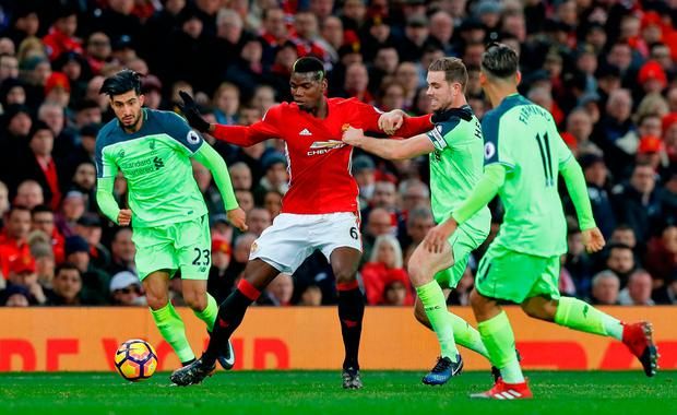 Manchester United's Paul Pogba (centre) and Liverpool's Jordan Henderson (2nd right) battle for the ball. Photo credit: Martin Rickett/PA Wire