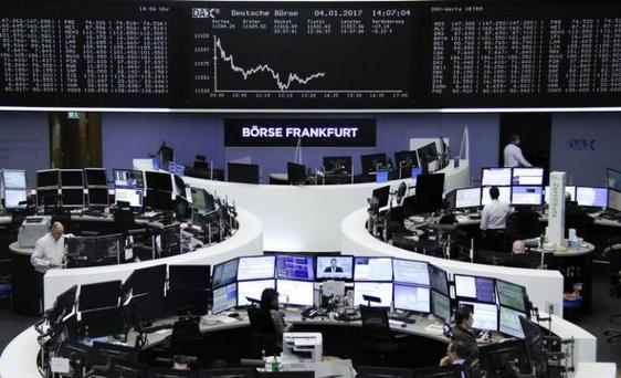 Traders work at their desks in front of the German share price index, DAX board, at the stock exchange in Frankfurt, Germany, January 4, 2017. REUTERS/Staff/Remote