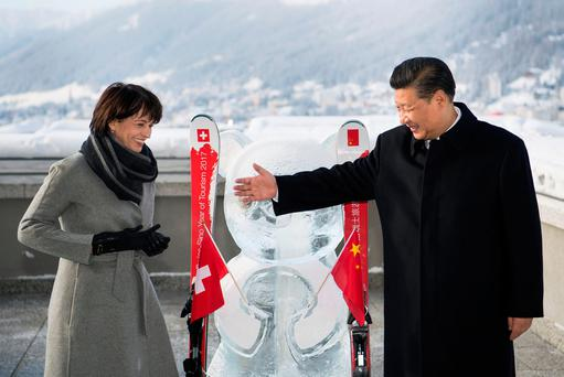 Swiss President Doris Leuthard stands next to China's President Xi Jinping as they launch the Swiss-Sino year of tourism next to a panda ice sculpture on the side line of the 47th annual meeting of the World Economic Forum (WEF) in Davos, Switzerland, January 17, 2017. REUTERS/Laurent Gillieron/Pool