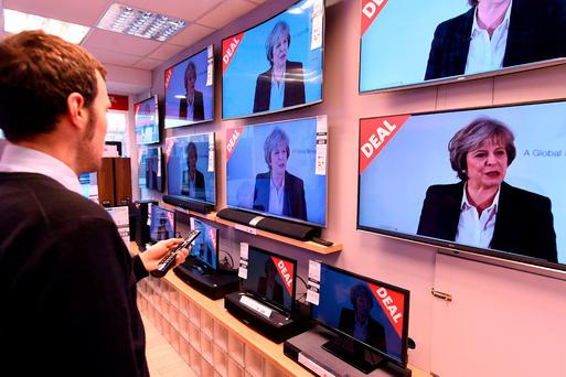 An employee changes the channels of televisions, on display in a store for sale in Liverpool, as they show a live speech by British prime minister Theresa May on her government's plans for Brexit. Photo: Getty Images