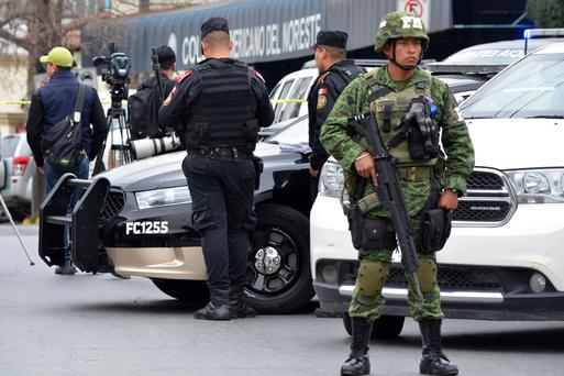 A soldier and police stand guard outside at a private school in Monterrey, Mexico, Wednesday, Jan. 18, 2016. A 15-year-old student opened fire with a gun at the school, hitting a teacher and two other students in the head before killing himself. (AP Photo/Emilio Vazquez)