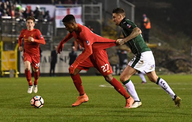 Plymouth Argyle's Sonny Bradley in action with Liverpool's Divock Origi Picture: Reuters