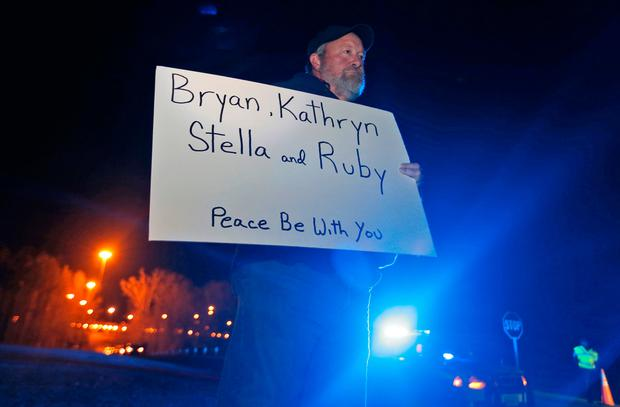Staunton Va., resident, Chuck Troutman, holds a sign in remembrance of the Harvey family outside the Greensville Correctional Center in Jarratt, Va., Wednesday, Jan. 18, 2017.(AP Photo/Steve Helber)