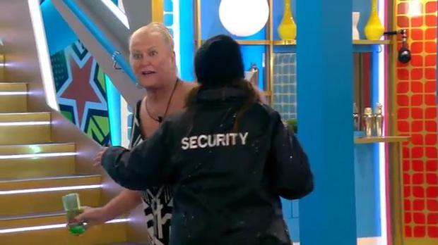 Kim Woodburn is escorted from the Celebrity Big Brother house by a female guard