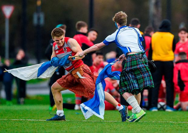 Glenstal Abbey supporter Darren Halpenny and St Clement's Eoghan Herdman tussle for possession of a flag during their schools' Munster Senior Cup clash. Photo: Diarmuid Greene/Sportsfile