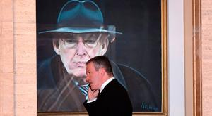 Sinn Féin's Conor Murphy, who has been considered as a possible replacement for Martin McGuinness, talks on his phone as he walks past a painting of the late DUP leader Ian Paisley at Stormont. Photo: Charles McQuillan, Getty Images