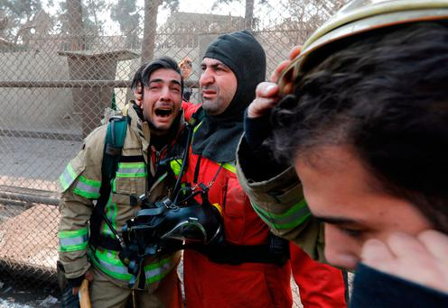 A firefighter consoles his comrade after the collapse of Iran's oldest high-rise, the 15-storey Plasco building in downtown Tehran. Photo: AFP/Getty Images