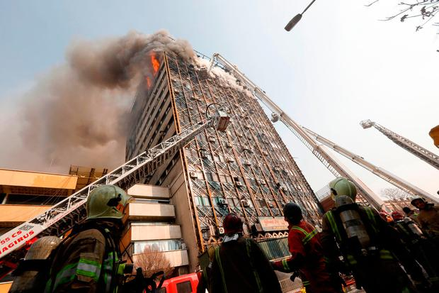 Firefighters battle a blaze that engulfed Iran's oldest high-rise, the 15-storey Plasco building in downtown Tehran. Photo: AFP/Getty Images