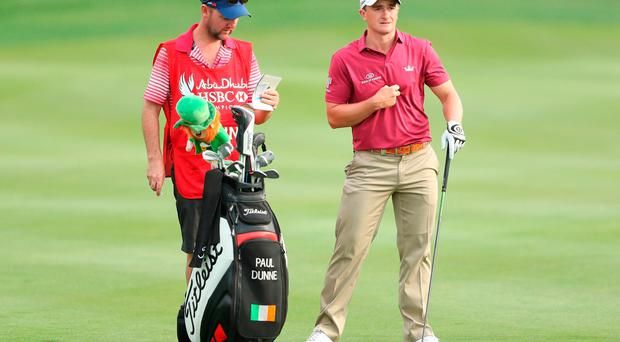 Paul Dunne of Ireland speaks with his caddie on the 8th hole
