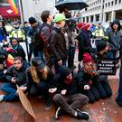 Demonstrators sit on sidewalk attempting to block people entering a security checkpoint, Friday, Jan. 20, 2017, ahead of President-elect Donald Trump's inauguration in Washington. ( AP Photo/Jose Luis Magana)