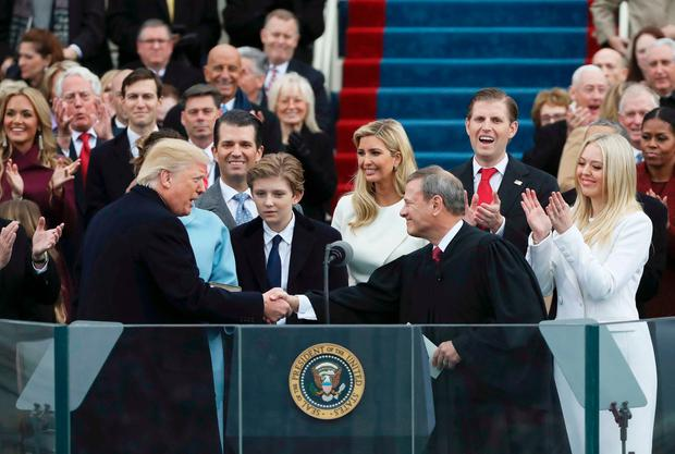 President Donald Trump shakes hands with Justice John Roberts (R) after taking the oath at inauguration ceremonies swearing in Trump as the 45th president of the United States on the West front of the U.S. Capitol in Washington, U.S., January 20, 2017. REUTERS/Carlos Barria