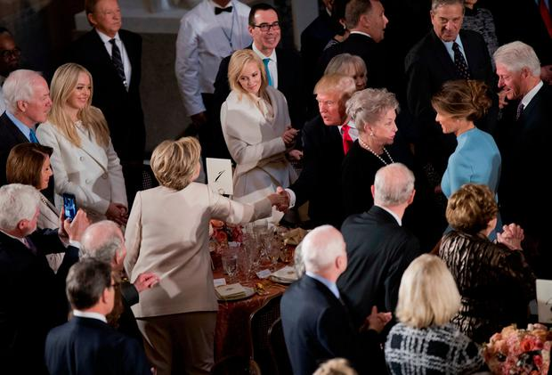 Newly sworn in President Donald Trump with his wife first lady Melania Trump, shakes hands with Hillary Clinton, as they arrive for the inaugural luncheon at the Statuary Hall in the Capitol, Friday, Jan. 20, 2017, in Washington. (AP Photo/Manuel Balce Ceneta)