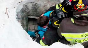 Rescuers pull survivors, including a young boy and a woman, from the Italian hotel buried by the avalanche. Photo: Italian Firefighters/ANSA via AP