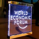 Attendees walk past a sign in the Congress Hall during the annual meeting of the World Economic Forum (WEF) in Davos, Switzerland