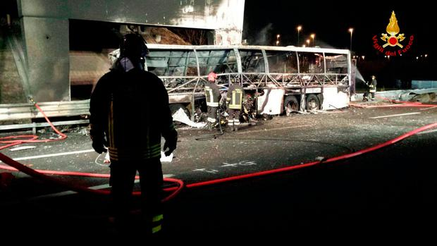 Firefighters inspect the burned hulk of a bus that crashed and burst into flames near Verona, northern Italy, Saturday, Jan. 21, 2017. (Italian Firfighters/ANSA via AP)