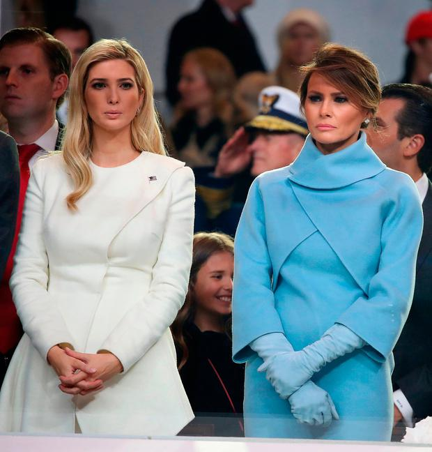 First lady Melania Trump (R), stands with Ivanka Trump as a parade passes the inaugural parade reviewing stand in front of the White House on January 20, 2017