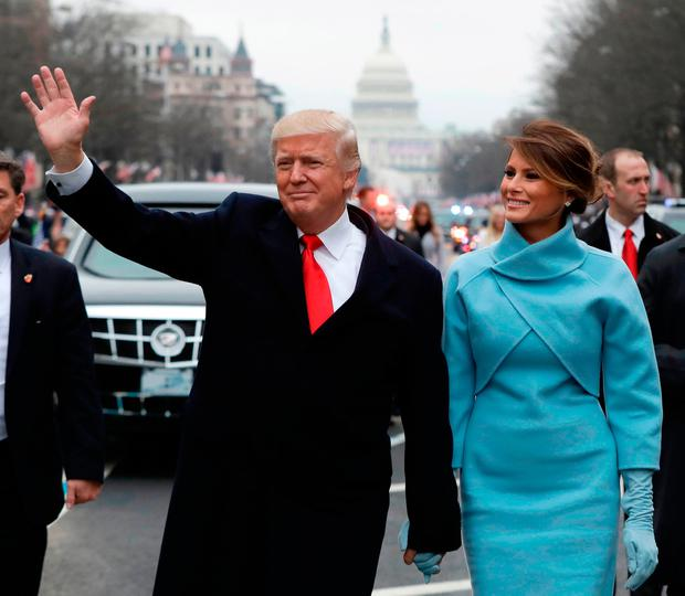 President Donald Trump gestures as he walks with first lady Melania Trump  during the inauguration parade