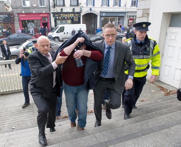Anthony Lambe pictured being lead to a special sitting of court in Dundalk where he was charged with the murder of Irene White. Picture Ciara WIlkinson.