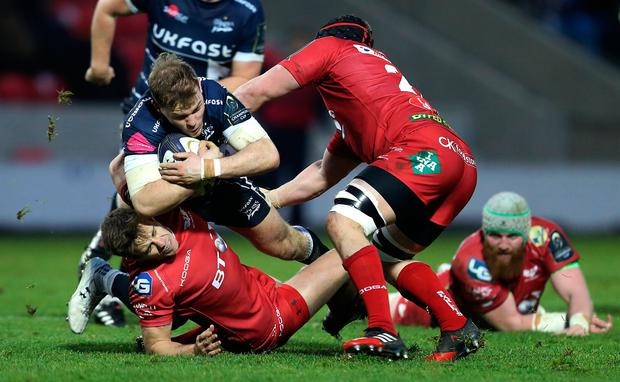 Will Addison of Sale Sharks is tackled by Aled Thomas and Will Boyde of Scarlets. Photo: Reuters