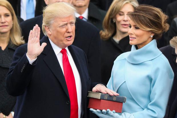 Donald Trump takes the oath of office as his wife Melania holds a bible during his inauguration Photo: REUTERS/Lucy Nicholson