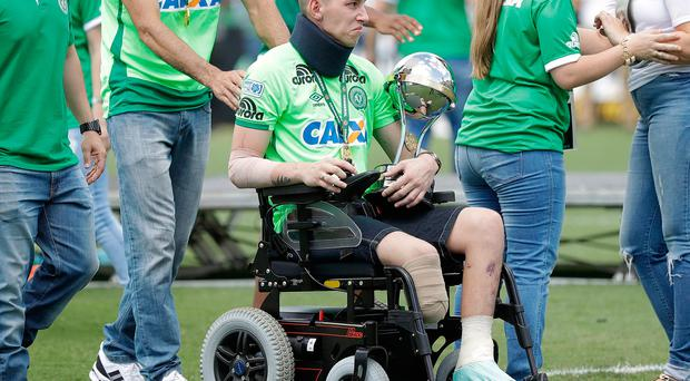 Chapecoense goalkeeper Follmann, one of the three players that survived the air crash almost two months ago, is wheeled on the pitch as he carries the Sudamericana trophy, during the Sudamericana trophy award ceremony prior to a match against Palmeiras, in Chapeco, Brazil
