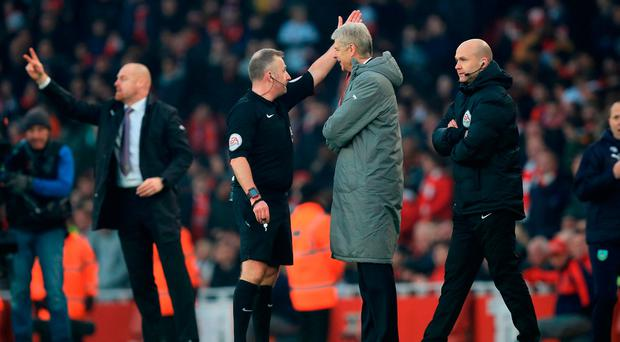 Referee Jonathan Moss (left) sends Arsenal manager Arsene Wenger (right) to the stands