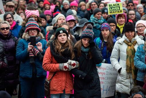 A woman linked arm-in-arm wipes away a tear as demonstrators gather in support of the Women's March on Washington in Halifax. Photo: Darren Calabrese/The Canadian Press via AP