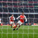 Alexis Sanchez dinks the ball down the middle of the goal to score past Burnley's Tom Heaton and win the game for Arsenal. Photo: Reuters / Dylan Martinez
