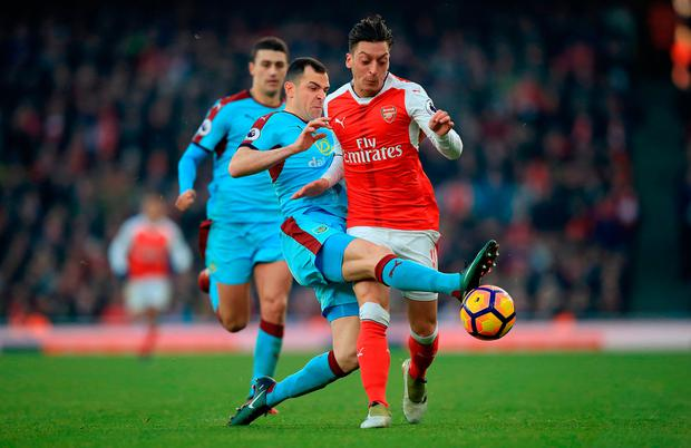 Burnley's Dean Marney (left) and Arsenal's Mesut Ozil (right) battle for the ball. Photo credit: Mike Egerton/PA Wire
