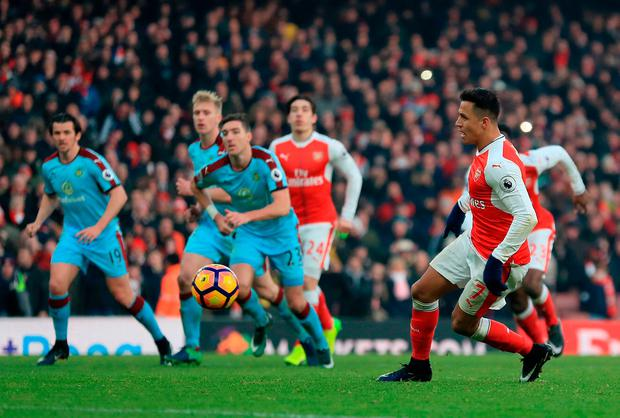 Arsenal's Alexis Sanchez (right) scores a penalty. Photo credit: Mike Egerton/PA Wire