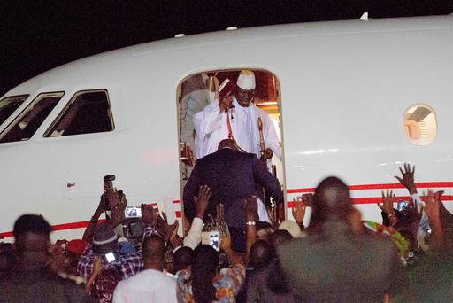 Gambia's defeated leader Yahya Jammeh waves to supporters as he departs at Banjul airport. Image: AP Photo/Jerome Delay
